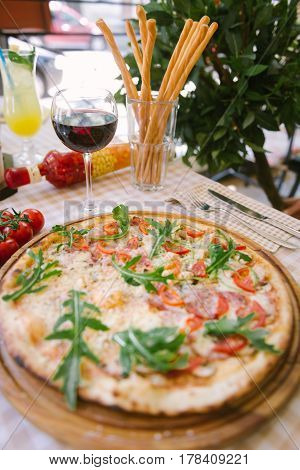 Pizza with cheese, tomato and meat, with glass of wine on served table with plaid tablecloth
