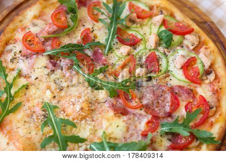 Pizza with cheese, tomato, squash, petals of arugula and meat, closeup