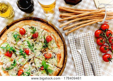 Tasty pizza with cheese, tomato and meat, with glass of beer and thin baguette on served table with plaid tablecloth