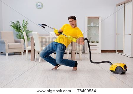Man playing virtual guitar with vacuum cleaner