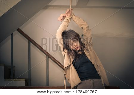 Female Hostage are tied up with ropes hanging on abandoned building ladders Vintage tone