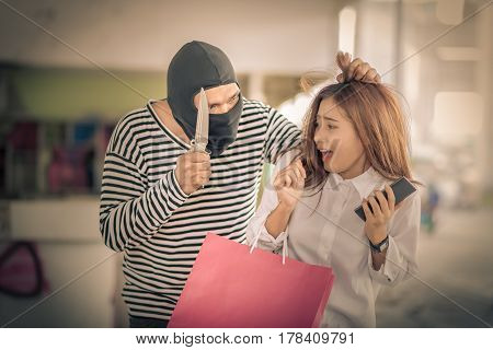 Thief stealing young woman shopping bag and threatening with knife Vintage tone
