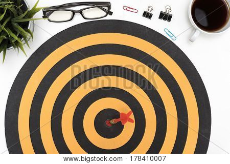 Dart target arrow hitting on bullseye in dartboard over office desk table background with eye glasses pen pencil computer and cup of coffee