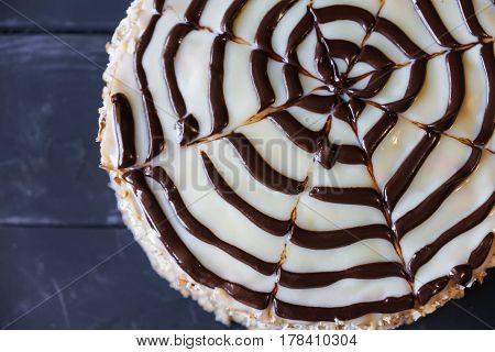 Delicious cake with nut chip and dark chocolate on white chokolate decoration, top view