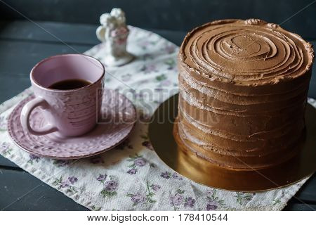 Delicious cake in chocolate sauce with cup of tee, on tender tablecloth