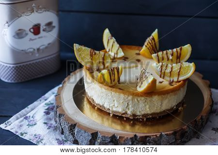 Delicious cake on wooden tray with orange wedges and chocolate sauce