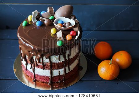 Beautiful cake with m-n-m, kinder, chocolate sauce and peace of chocolate, with tangerines near