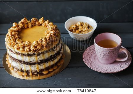 Delicious cake with caramel popcorn and caramel sauce and plate with popcorn and pink cup of tee