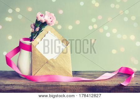 Mother's day card pink carnations in a white vase with ribbon on a wooden table note with the inscription