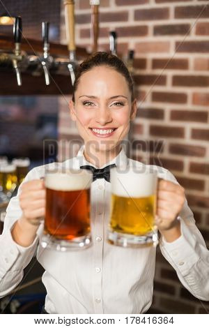 A close up image of an attractive female bartender holding two beers in a pub