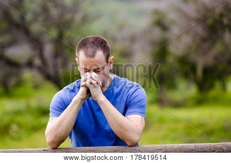 Man praying with his head down and hands together, alone in nature embracing God`s creation.