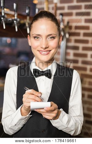 Barmaid taking orders on notepad in bar