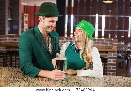 Man and woman looking at each other while holding beers in a bar