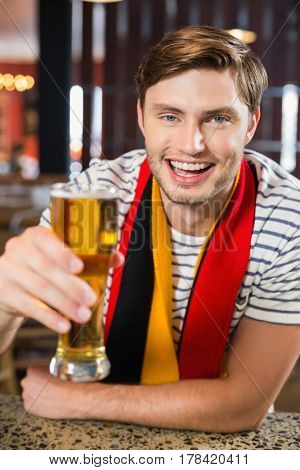 Man toasting a beer while looking at the camera