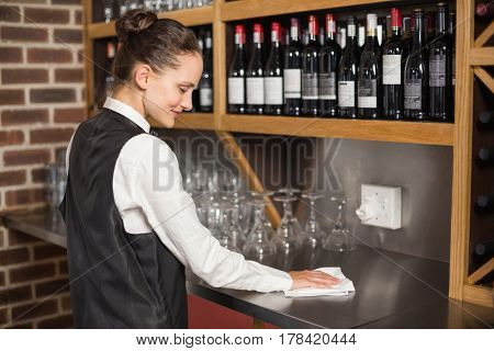 Barmaid cleaning table in a bar