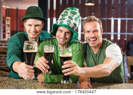 Men toasting with beers in a bar