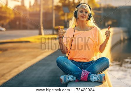 Young teenage style woman sitting on stone quay at morning sunrise and listening music