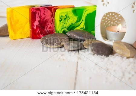 Spa still life with salt stone and red yellow and green soap with aroma lamp on the white wooden table with copy space