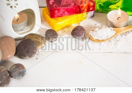 Still life for spa with salt stone and three soap pieces with aroma lamp on the white wooden background with copy space
