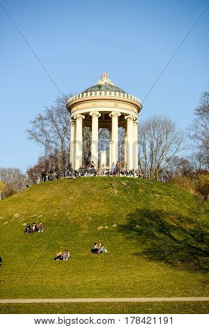 Munich,Germany-March 232017:People relax while sunbathing at the Monopteros in the Englischer Garten