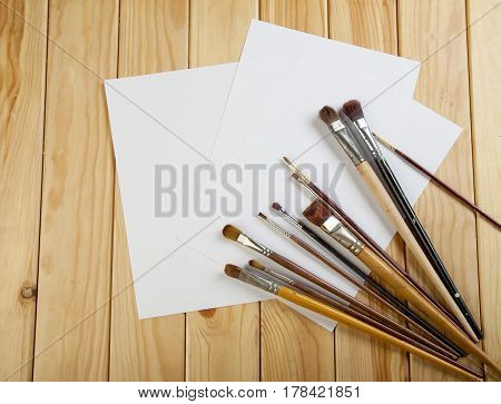 Brushes And Three White Sheet Of Paper On A Wooden Table