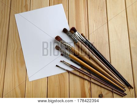 Brushes And White Sheet Of Paper On A Wooden Bg