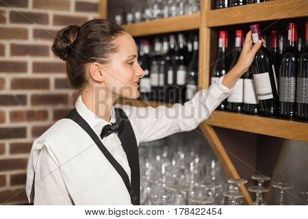 Beautiful barmaid taking red wine bottle out of shelf