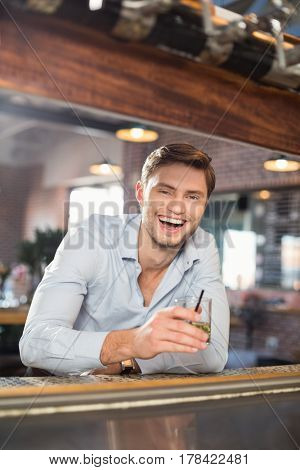 Handsome man holding whiskey while smiling