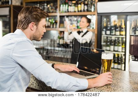 Handsome man working in a bar on a laptop with beer in his hand