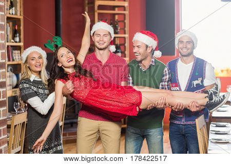 Friends with Christmas hats carrying a woman in a bar