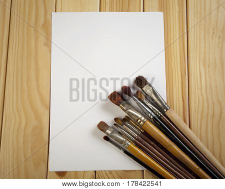 Brushes And White Sheet Of Paper On A Wooden Table