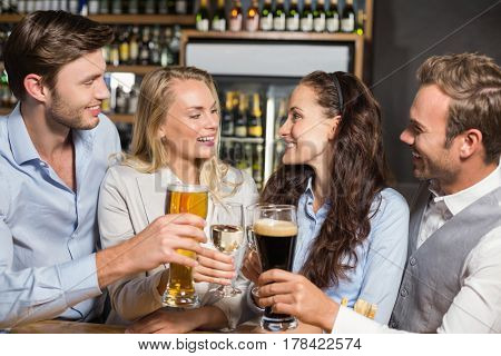 Attractive friends toasting women with white wine and men with beer