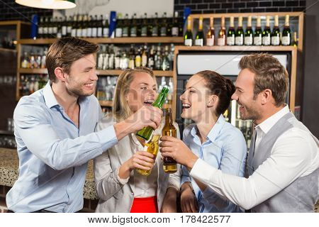 Attractive friends toasting with bottles of beer in a bar