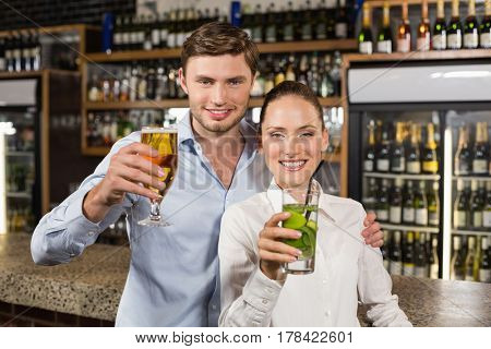Attractive woman and man hugging with beverages in hands