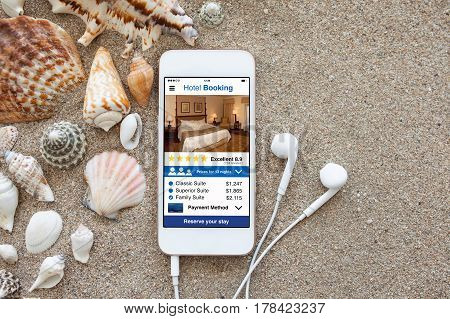 phone with app hotel booking screen and headphones on sand shells