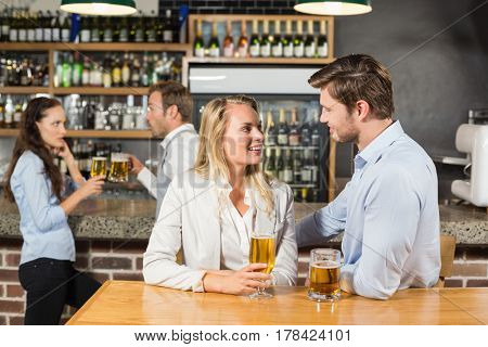 Attractive couples talking and holding beer at a bar