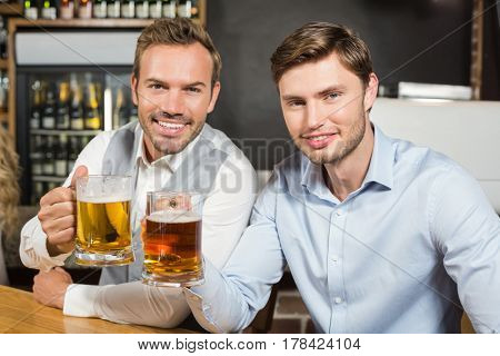Handsome men toasting with beers in a bar