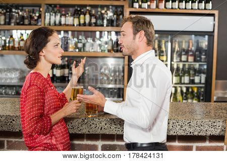 Attractive couple holding beer and arguing in a bar