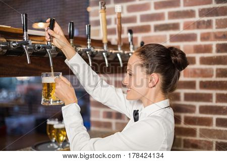Attractive barmaid pouring beer in a glass