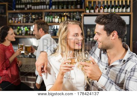 Attractive couple looking at each other and toasting with white wine