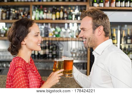 Attractive couple toasting beer and smiling at each other at a bar