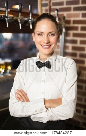 Attractive barmaid with arms crossed at a bar