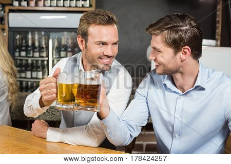 Handsome men toasting while looking at each other in a bar