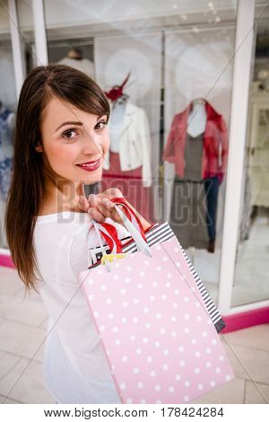 Portrait of woman holding shopping bags while shopping in mall