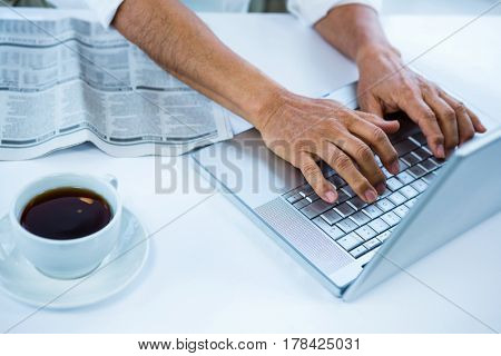 Businessman typing on his computer in office