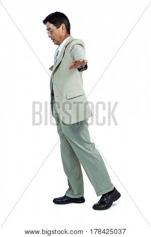 Focused businessman walking straight ahead on an invisible tightrope