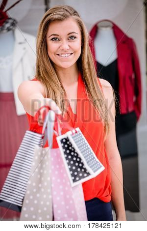 Portrait of woman showing her shopping bags in mall
