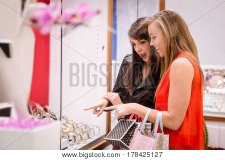 Two beautiful women talking and looking at a display of watches in shop