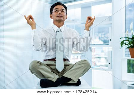 Peaceful asian businessman relaxing in office