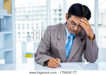 Worried asian businessman on his desk in office
